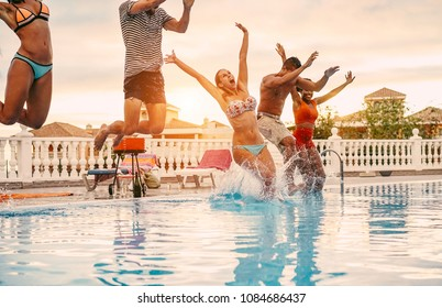 Group of happy friends jumping in pool party at sunset - Young diverse culture people having fun in tropical vacation - Holiday, youth lifestyle and friendship concept - Main focus on blond woman face