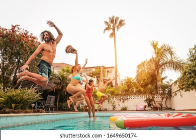 Group happy friends jumping in pool at sunset time - Crazy young people having fun making party in exclusive tropical house - Summer holidays vacation and youth culture lifestyle concept