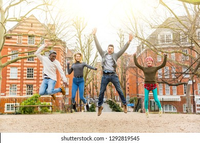 Group of happy friends jumping together at park. Mixed races group having fun in London on a cloudy day. Lifestyle and friendship concepts