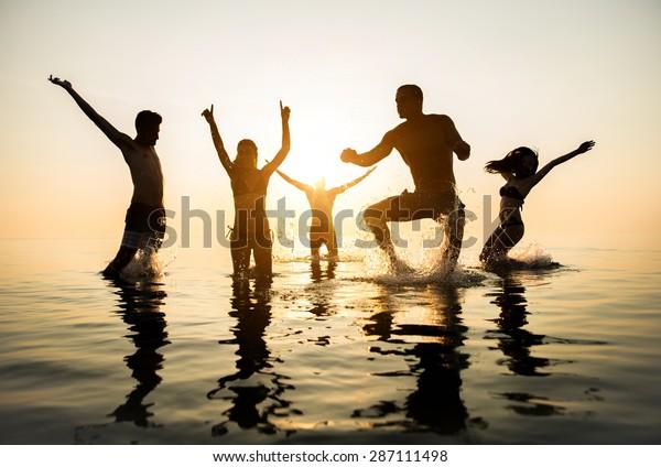Grupo de amigos felices saltando al agua al atardecer - Silhouettes de gente activa bailando y divirtiéndose en la playa de vacaciones