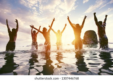 Group of happy friends jumps and having fun at sunset sea beach. Tropical travel concept with peoples silhouettes