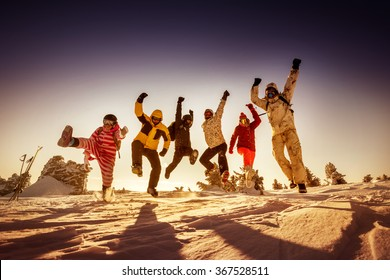Group of happy friends jumps on background of sunset. Sheregesh resort, Siberia, Russia
