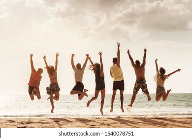 Group of happy friends jumps together at sunset sea beach. Tropical vacations concept