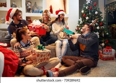 Group happy of friends laughing and sharing Christmas gifts