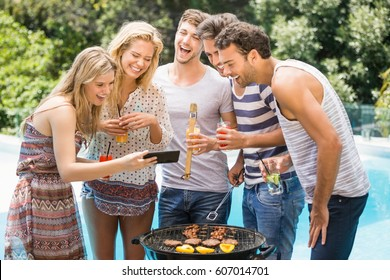 Group of happy friends looking at mobile phone while preparing barbecue near pool