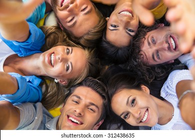 Group of happy friends lying together in a circle