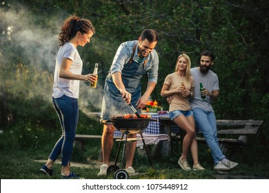 Group of happy friends making barbecue outdoors