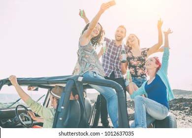 Group of happy friends making party on a jeep car - Young people having fun drinking champagne and taking photo selfie during their road trip - Friendship, party, youth addiction lifestyle concept