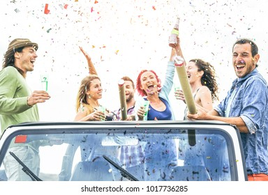Group of happy friends making party throwing confetti on convertible jeep car - Young people celebrating and having fun drinking champagne and laughing together outdoor - Youth lifestyle concept