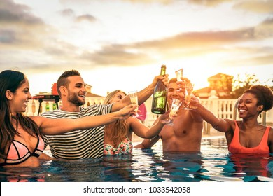 Group of happy friends making a pool party cheering with champagne at sunset - Young people laughing and having fun toasting with sparkling wine in luxury tropical resort - Youth lifestyle concept