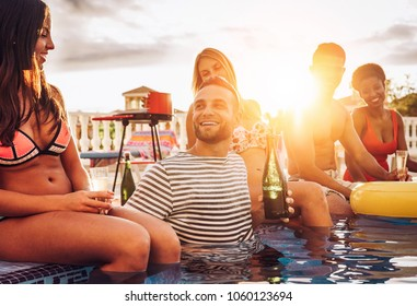 Group of happy friends making a pool party drinking champagne at sunset on vacation - Young people laughing and having fun with sparkling wine in luxury tropical resort - Youth lifestyle concept