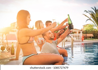 Group of happy friends making a pool party at sunset - Young people laughing and having fun drinking champagne at barbecue poolparty in vacation - Friendship, holidays, youth lifestyle concept