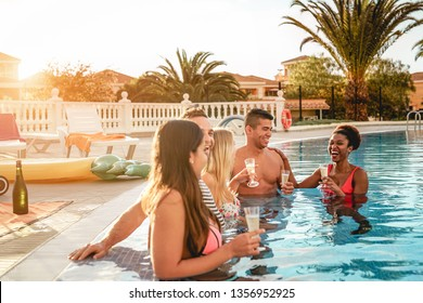 Group of happy friends making a pool party at sunset - Millennial young people laughing and having fun drinking champagne in the pool - Friendship, holidays and summer youth lifestyle concept