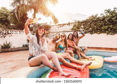 Group of happy friends making pool party taking selfie with mobile smartphone - Young people having fun in exclusive summer tropical vacation - Friendship, tech, holidays and youth lifestyle concept