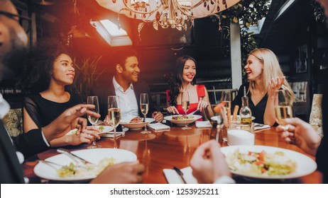 Group of Happy Friends Meeting and Having Dinner. Celebrating with Friends. Party Dinner Table. Enjoying Meal In Restaurant. Restaurant Chilling Out Classy Lifestyle Reserved Concept.