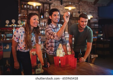 Group of happy friends playing game in pub