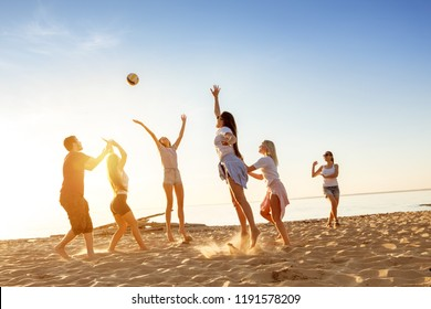 Group of happy friends plays with ball at sunset beach. Weekend activity concept
