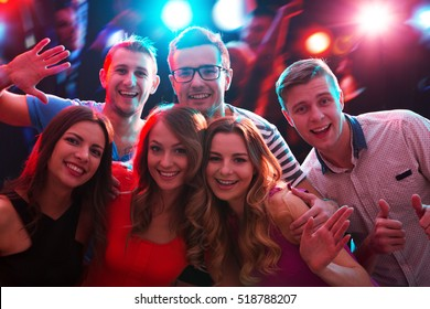 Group of happy friends posing in the night club