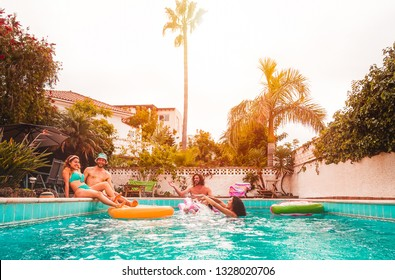 Group of happy friends relaxing in swimming pool - Young people having fun floating on air lilo during summer tropical vacation - Friendship, holidays and youth lifestyle concept