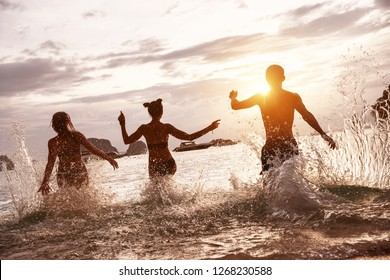 Group of happy friends run and jump at sunset sea beach. Tropical vacations concept