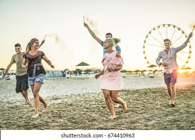 Group of happy friends running on the beach with fireworks sparklers - Young people having fun in summer vacation - Youth and friendship concept - Main focus on right blond woman - Contrast filter