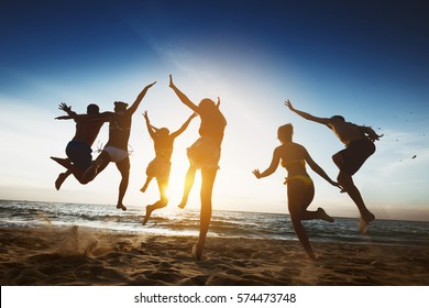Group of happy friends runs and jumps at sunset beach. Friendship, holidays or teamwork success concept