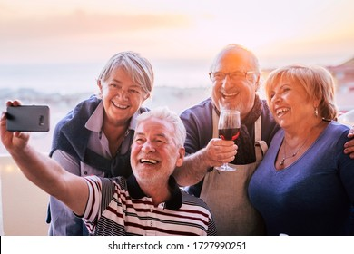 Group of happy friends senior people have fun together with social contact doing selfie with a smart phone - mature celebrate in outdoor - retired lifestyle and men women smile and laugh in friendship
