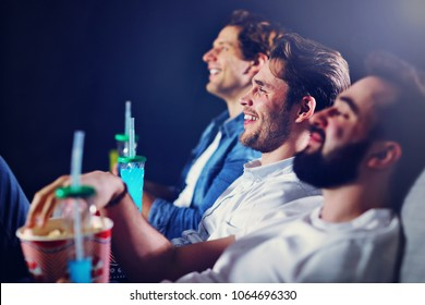 Group of happy friends sitting in cinema watch film and eating popcorn