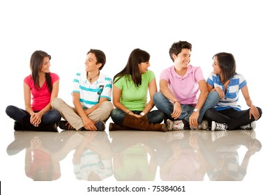 Group of happy friends sitting on the floor and talking ? isolated