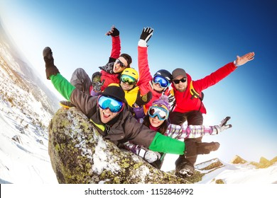 Group of happy friends skiers and snowboarders having crazy fun at ski resort