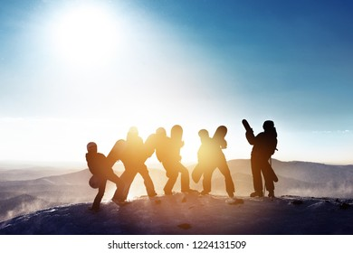 Group of happy friends skiers and snowboarders are having fun. Five silhouettes with ski and snowboards on mountain top at ski resort