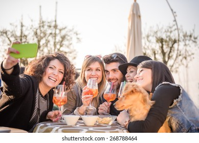 group of happy friends with smartphone taking selfie and drinking aperitif at cafe