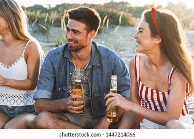 Group of happy friends spending time together at the beach, having picnic, toasting with beers and laughing