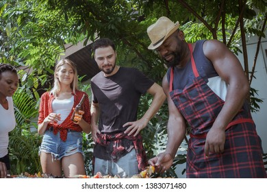 Group of happy friends standing eating and drinking beers at barbecue dinner camping in nature and having meal together outdoor as summer lifestyle, food and friendship concept