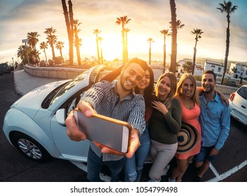 Group of happy friends standing in front of convertible car and taking selfie with mobile phone - Young people having fun in vacation at sunset - Friendship, tech, youth holidays lifestyle concept
