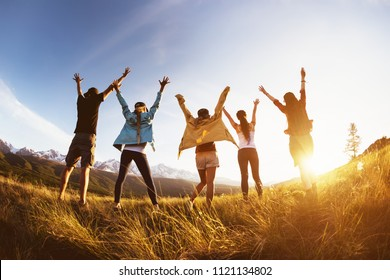 Group of happy friends stands against mountains sunset with raised arms and having fun