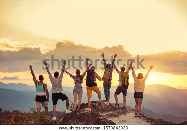 Gruppe glücklicher Freunde steht mit aufgewachsenen Armen am Sonnenuntergang Berg und genießt Sonnenuntergang
