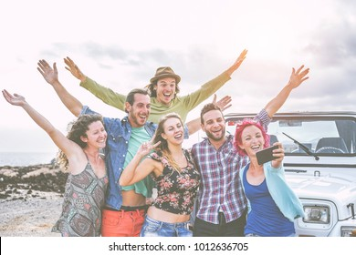 Group of happy friends taking a selfie using mobile smart phone during a road trip with car - Travel people having fun spreading hands up while taking self photos in desert - wanderlust concept