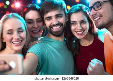Group of happy friends taking selfie in a night club