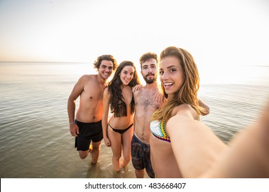 Group of happy friends taking a selfie at the beach. Concept about technology, people and lifestyle