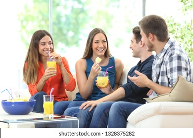 Group of happy friends talking eating chips and drinking refreshments sitting on a couch in the living room at home