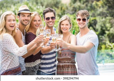 Group of happy friends toasting champagne glasses outdoors
