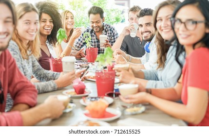 Group of happy friends toasting coffee and cappuccino at bar cafe - Young hipster people enjoying breakfast drinking hot beverage - Friendship and food concept - Focus on indian man - Warm filter