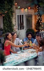 Un grupo de felices amigos tostando en la fiesta de cumpleaños al aire libre en un hermoso atardecer de verano. Tiempo de amistad de calidad