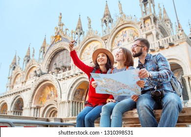 Group of happy friends travelers with map on San Marco Square in Venice. Vacation and holidays in Italy and Europe concept