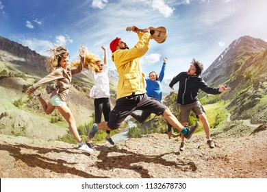 Group of happy friends with ukulele guitar is having fun and jumps against mountain during trekking. Music fun concept