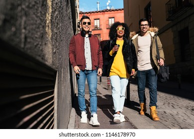 Group of happy friends walking in the street. Friendship concept