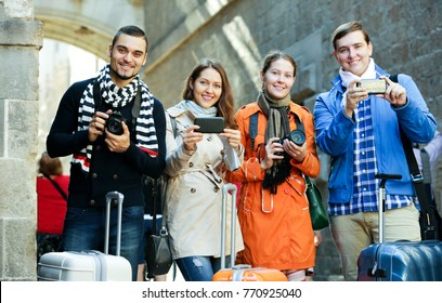 Group of happy friends walking through street with camera and smartphone