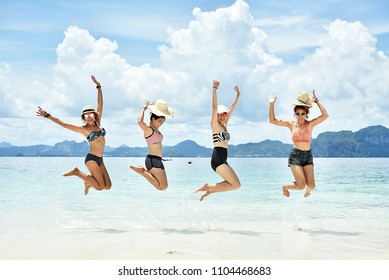 Group of happy friends wearing bikini , jumping and open arms on the beach,enjoying summer vacation Summer concept and multiethnic friendship.