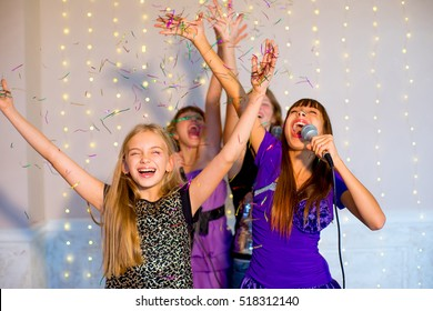Group of happy girls with headphones singing together on karaoke on background of lights